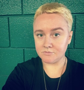 Selfie of Jesse Rice-Evans, a white femme with short blonde hair, against a brick wall painted green