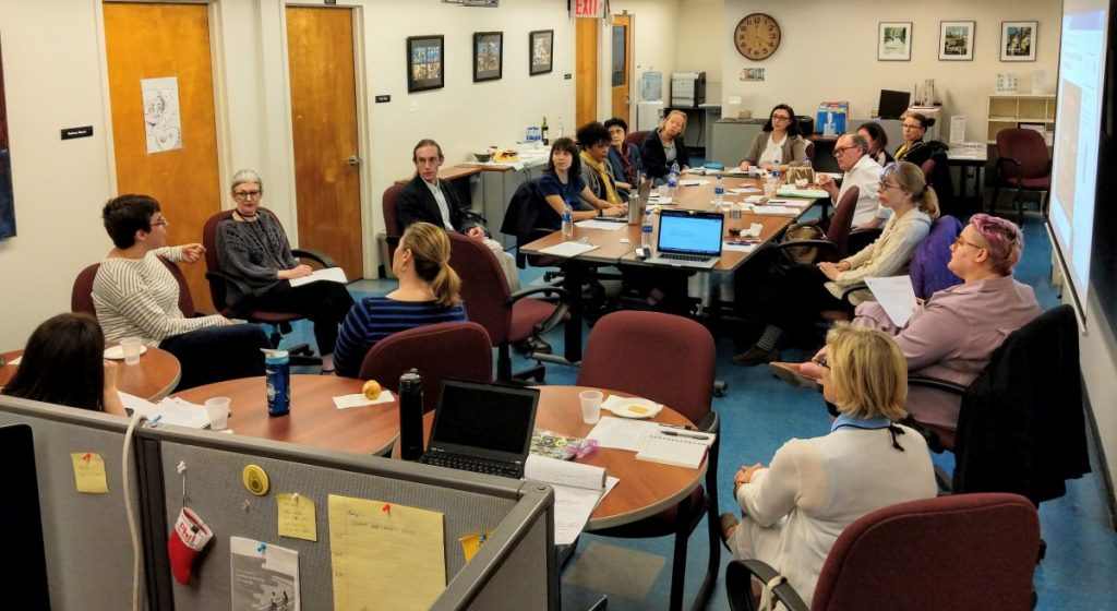 Wide photo of a group of faculty and staff around a large conference table at City Tech. The table is scattered with papers, laptops, and small plates with snacks.
