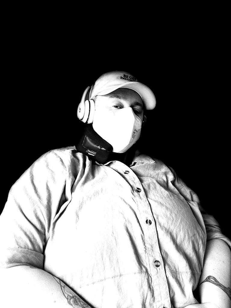 Photo by Zefyr Lisowski Bust portrait of Jesse, a white fat femme, in a cap and KN95 mask, wearing headphones, a soft cervical collar, and a button-down linen shirt, in grayscale. She has tattoos visible on both of her forearms.